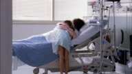 Medium shot young girl running to woman in hospital bed and hugging her