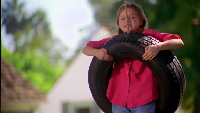 Medium shot young girl sitting in tire swing outdoors and smiling at CAM