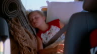 Medium shot young girl sleeping in backseat of minivan