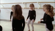 Medium shot young girls in leotards and tights doing movements and sitting down in ballet class