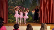 Medium shot young girls in tutus dancing out onto stage / teacher instructing them to turn and pose / curtsying / woman taking photos from audience
