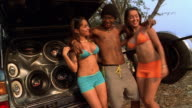 Medium shot young man and 2 young women dance next to massive car speakers