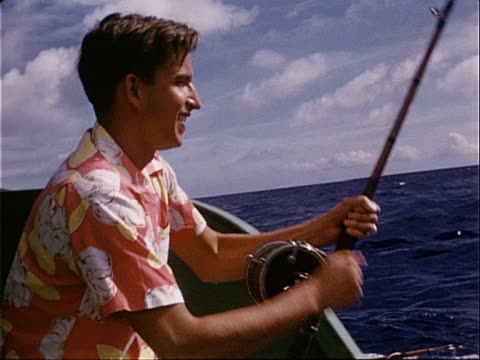 1953 Medium shot Young man fishing in ocean during fishing trip / Hawaii, USA