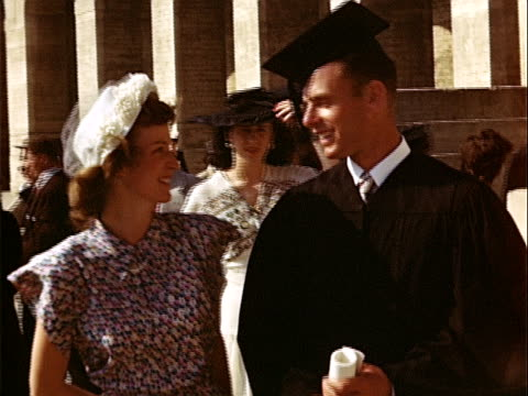 1949 Medium shot Young man graduate holding diploma and young woman attending graduation at University of California campus / Westwood, Los Angeles, California, USA
