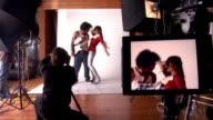 Medium shot young man posing for photographer and dancing in studio
