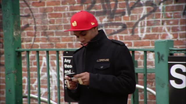 Medium shot Young man using electronic organizer near city subway sign / New York City, New York, USA