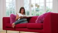 Medium shot young woman on sofa reading magazine/ London