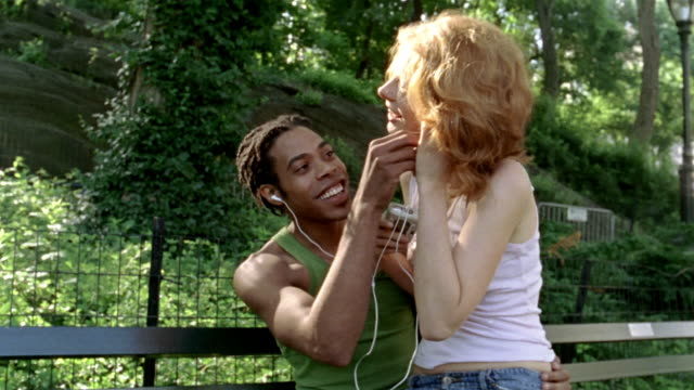 Medium shot young woman sharing earphones with boyfriend on park bench / New York City