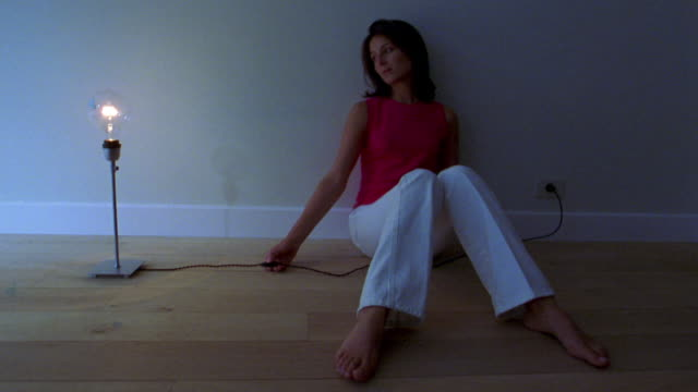 Medium shot young woman sitting on floor against wall in dark and switching light bulb lamp on floor on + off