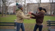 Medium shot Young women giving each other street handshakes in park / Williamsburg, Brooklyn, New York, USA