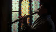 Medium shot zoom in clarinetist plays in profile w/stained glass windows in background