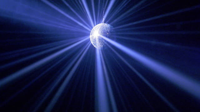 Medium shot zoom in mirror ball spinning and reflecting blue rays of light