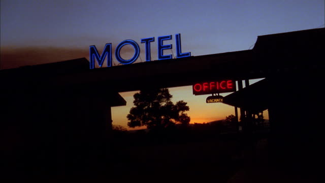 Medium shot zoom in neon motel and office sign at dusk