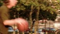 Medium shot zoom in pan young men playing basketball at Martin F. Tenahey Playground / New York City