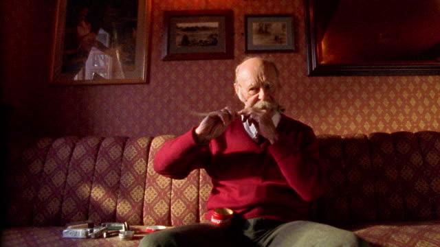 Medium shot zoom in senior British man waxing long hairs of handlebar mustache