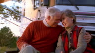 Medium shot zoom in senior couple smiling at CAM outdoors