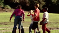 Medium shot zoom in tilt down girl sliding into base / arguing with boys