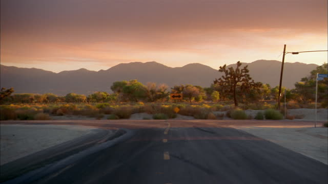 Medium shot zoom in to road sign on desert road w/mountains in background