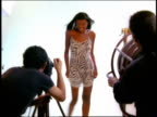 FAST MOTION medium shot zoom in zoom out Black model posing in studio for photographer and fan operator in foreground