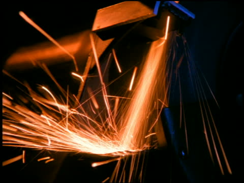 Medium shot zoom in zoom out metal bar being applied to grinder with sparks flying off