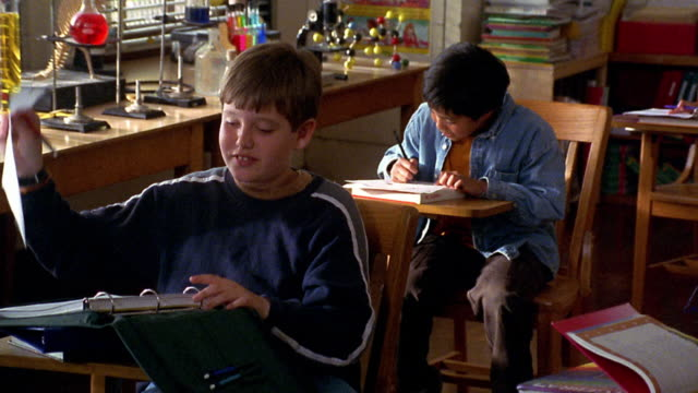 Medium shot zoom out boy rips sheet of paper from notebook and passes it to boy behind him who laughs