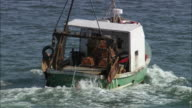 Medium shot zoom out fishing boat dropping lobster traps in North Sea near Arbroath Cliffs/ Aberdeenshire, Scotland