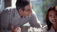 Medium shot zoom out man discussing architecture building model w/Asian man and woman