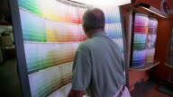 Medium shot zoom out man looking at paint samples / selecting one and nodding
