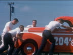 1959 medium shot zoom out teenage boys pushing red hot rod off transport trailer