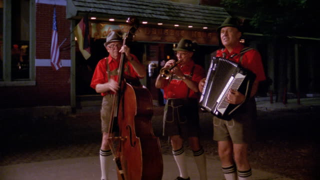 1990 medium shot zoom out three members of a German folklore band performing outside a restaurant / Columbus