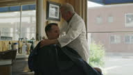 Medium slow motion panning shot of barber putting smock on customer / Pleasant Grove, Utah, United States