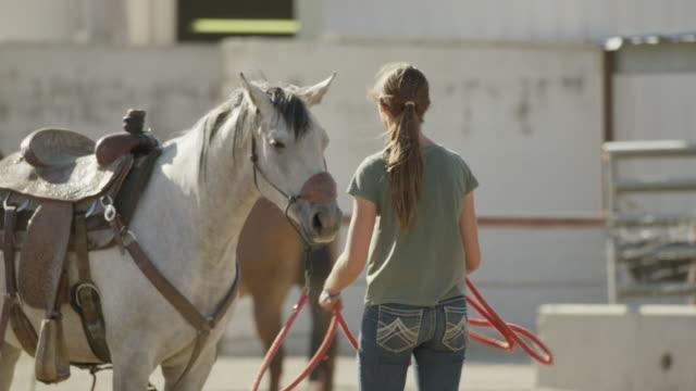 Medium slow motion panning shot of girl gathering rope and petting horse / Lehi, Utah, United States