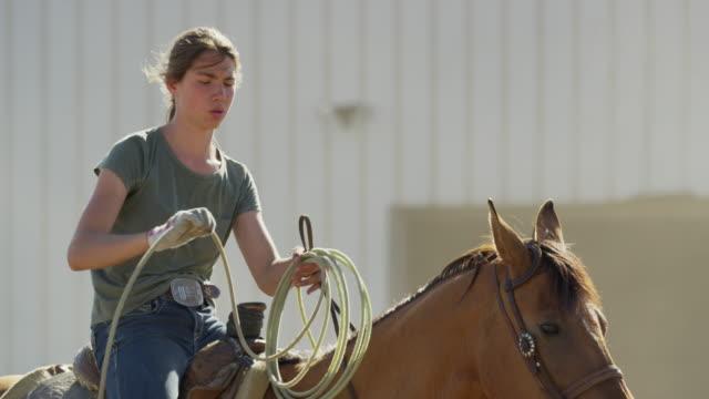 Medium slow motion panning shot of girl holding lasso on horse / Lehi, Utah, United States