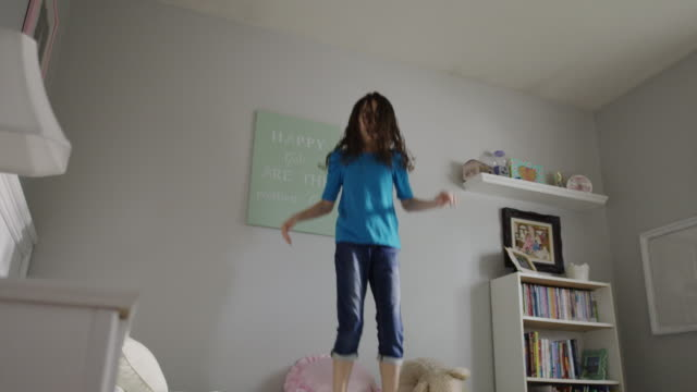 Medium slow motion panning shot of girl jumping on bed / Provo, Utah, United States