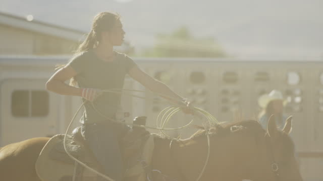 Medium slow motion panning shot of girl on horse holding lasso / Lehi, Utah, United States
