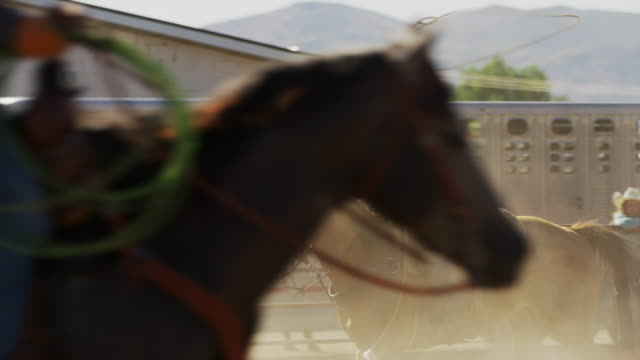 Medium slow motion panning shot of girl riding horse throwing lasso / Lehi, Utah, United States