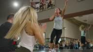 Medium slow motion panning shot of instructor leading exercise class / Orem, Utah, United States