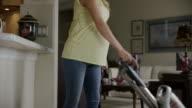 Medium slow motion panning shot of pregnant woman vacuuming house / Cedar Hills, Utah, United States