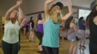 Medium slow motion panning shot of women dancing in exercise class / Orem, Utah, United States