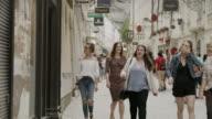 Medium slow motion panning shot of women window shopping in city / Salzburg, Austria