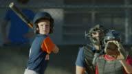 Medium slow motion shot of batter hitting baseball and running / American Fork, Utah, United States