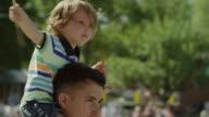 Medium slow motion shot of boy waving American flag at parade / American Fork, Utah, United States