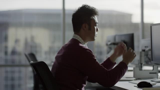 Medium slow motion shot of frustrated businessman sitting at desk / Lehi, Utah, United States