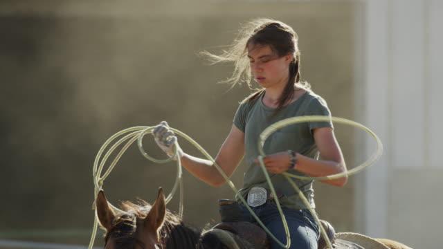 Medium slow motion shot of girl on horse holding lasso / Lehi, Utah, United States