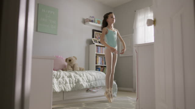 Medium slow motion shot of girl practicing ballet in bedroom / Provo, Utah, United States