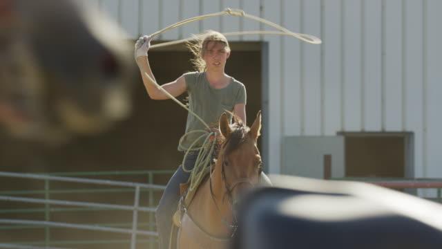 Medium slow motion shot of girl spinning lasso on horse / Lehi, Utah, United States