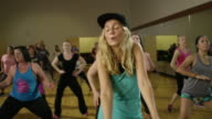 Medium slow motion shot of people dancing in exercise class / Orem, Utah, United States