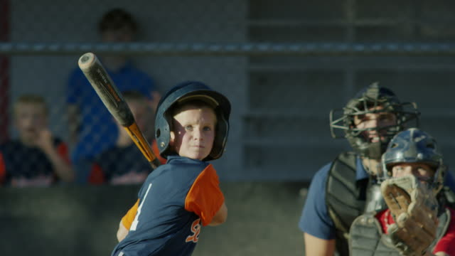 Medium slow motion shot of surprised batter hitting baseball and running / American Fork, Utah, United States