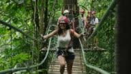 Medium slow motion shot of woman walking on wooden rope bridge / Quepos, Puntarenas, Costa Rica
