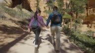 Medium slow motion tracking shot of couple hiking in desert / Bryce Canyon National Park, Utah, United States